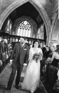Bride walking down the aisle wearing her bespoke sleeved lace wedding dress from Boho Bride, Stratford Upon Avon, Warwickshire
