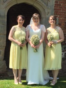 Bride wearing lace wedding dress with her bridesmaids in lemon yellow bridesmaid gowns