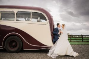 Amy and Josh's red and cream old fashioned wedding bus