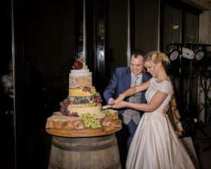 Bride and groom cutting tiered cheese wedding cake