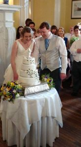 Alternative bride cutting cake at vintage wedding in Stratford-Upon-Avon