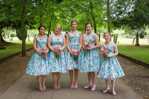 Bridesmaids wearing blue and pink, tea-length floral wedding dresses with pink shoes