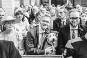 Guest hugging dog at church wedding in Warwickshire