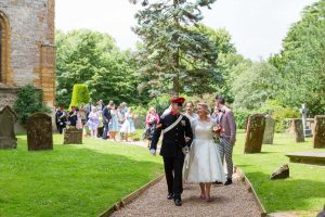 Bride wearing tea-length wedding dress and pink shoes at church wedding in Stratford-Upon-Avon