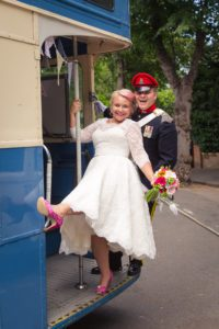 Bride wearing tea-length wedding dress with lace sleeves and pink shoes