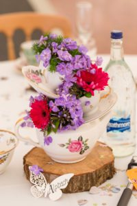 Red and purple flowers in vases at vintage wedding in Warwickshire