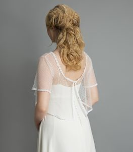 Model wearing wedding dress and polka dot bolero from the Freedom Collection at a bridal boutique in Stratford Upon Avon