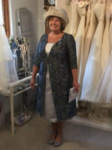 Mother of the bride wearing her bespoke, tailored jacket in bridal boutique in Stratford Upon Avon