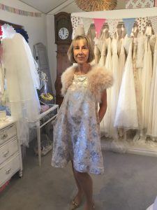 Mother of the bride wearing her bespoke, tailored dress and bolero in bridal boutique in Stratford Upon Avon