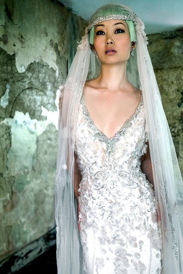 Heavily-embellished, elaborately designed silver coloured wedding dress with unique lace features, a plunging neckline and open back with keyhole feature back in Warwickshire, UK