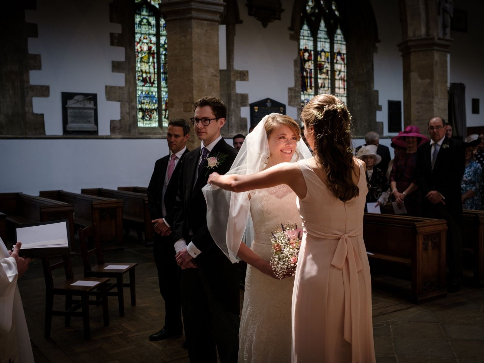 Bridesmaid removing veil from Boho Bride Harriet's face
