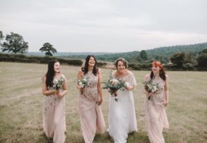 Bride at outdoor wedding with her bridesmaids wearing pink bridesmaid dresses