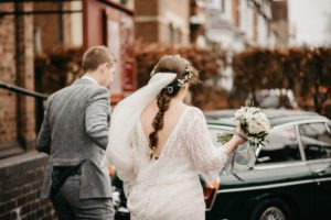 Bespoke, lace wedding dress with low back and sleeves and a long train. Wedding dress designed and created by Lola and Em bridal designers from Warwickshire in association with Boho Bride Boutique in Stratford Upon Avon