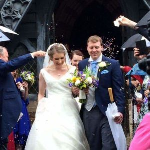 Bride walking out of wedding ceremony with groom, guests throwing confetti