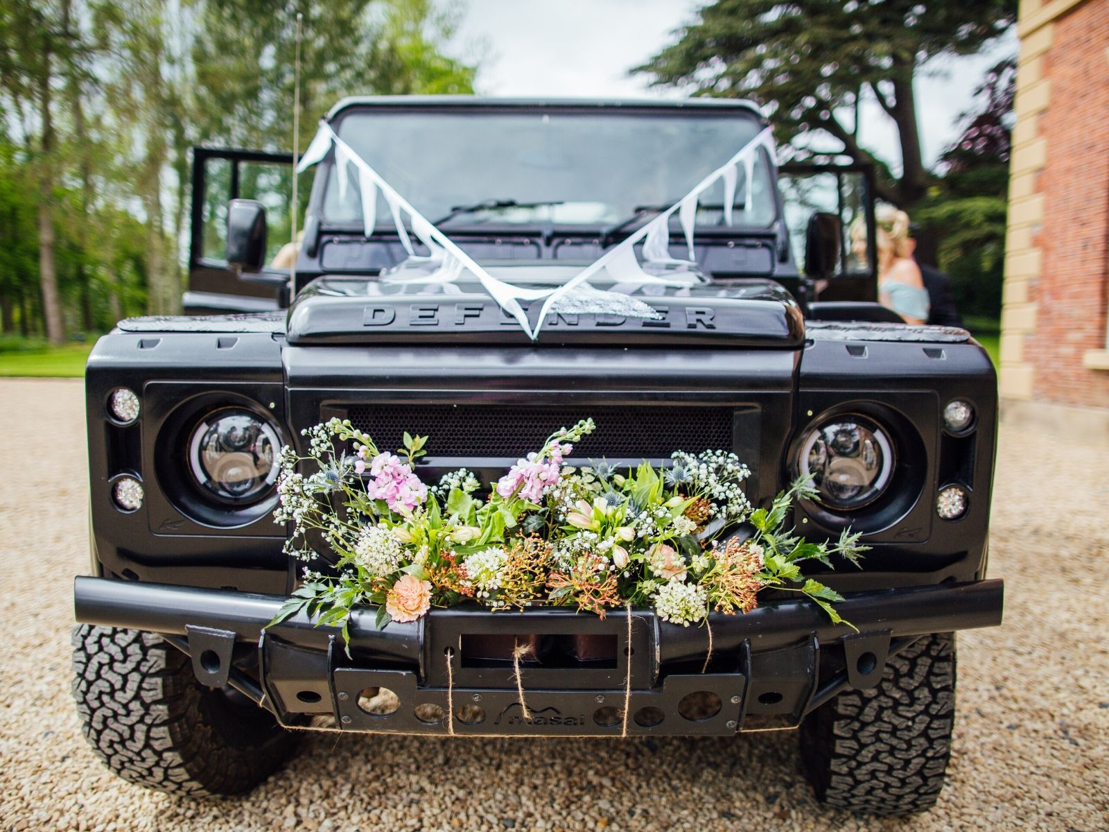 Land Rover wedding transport with bunting and flowers