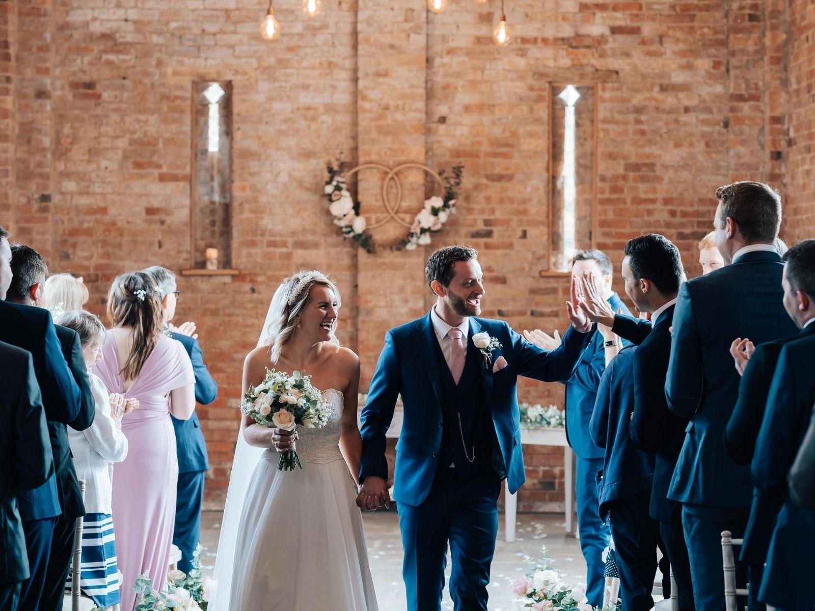 Bride holding wedding flowers leaving barn wedding ceremony