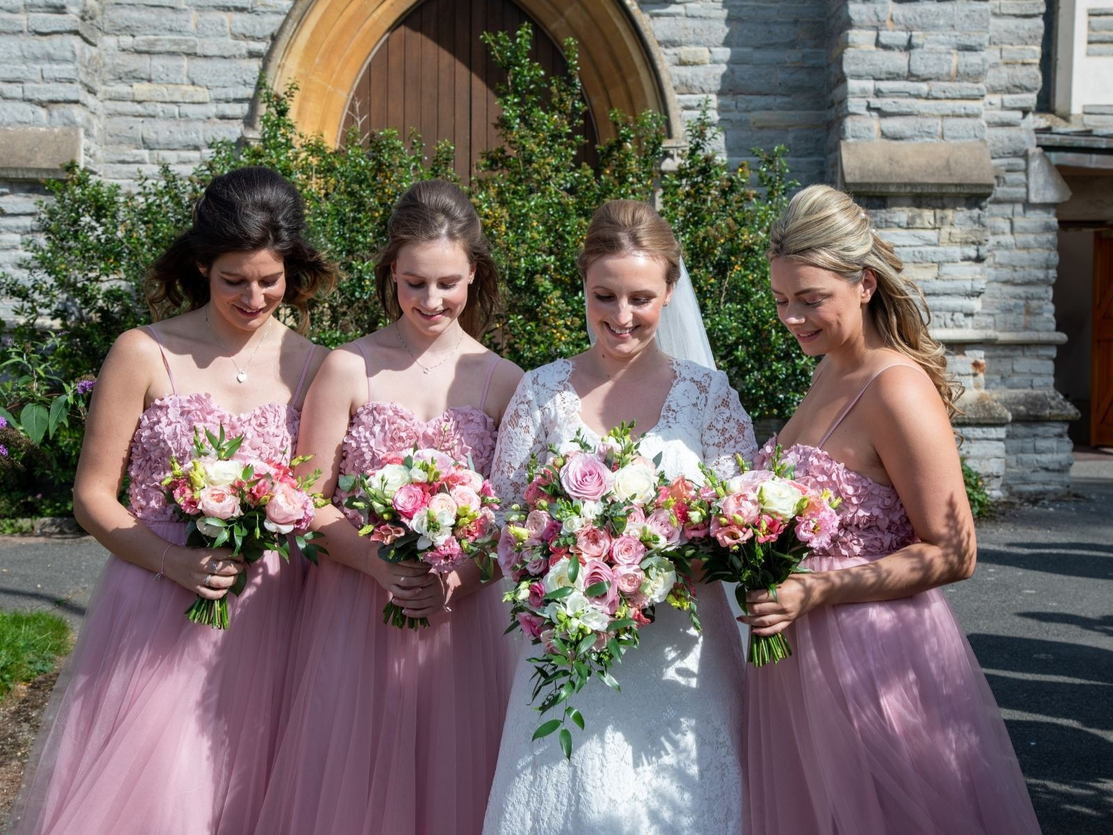 Boho bride with her bridesmaids in blush pink wedding dresses