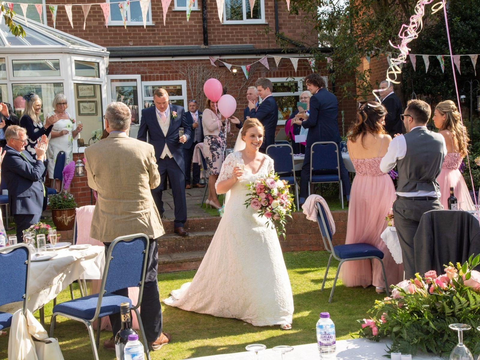 Rachel walking into her wedding reception in her parents' garden