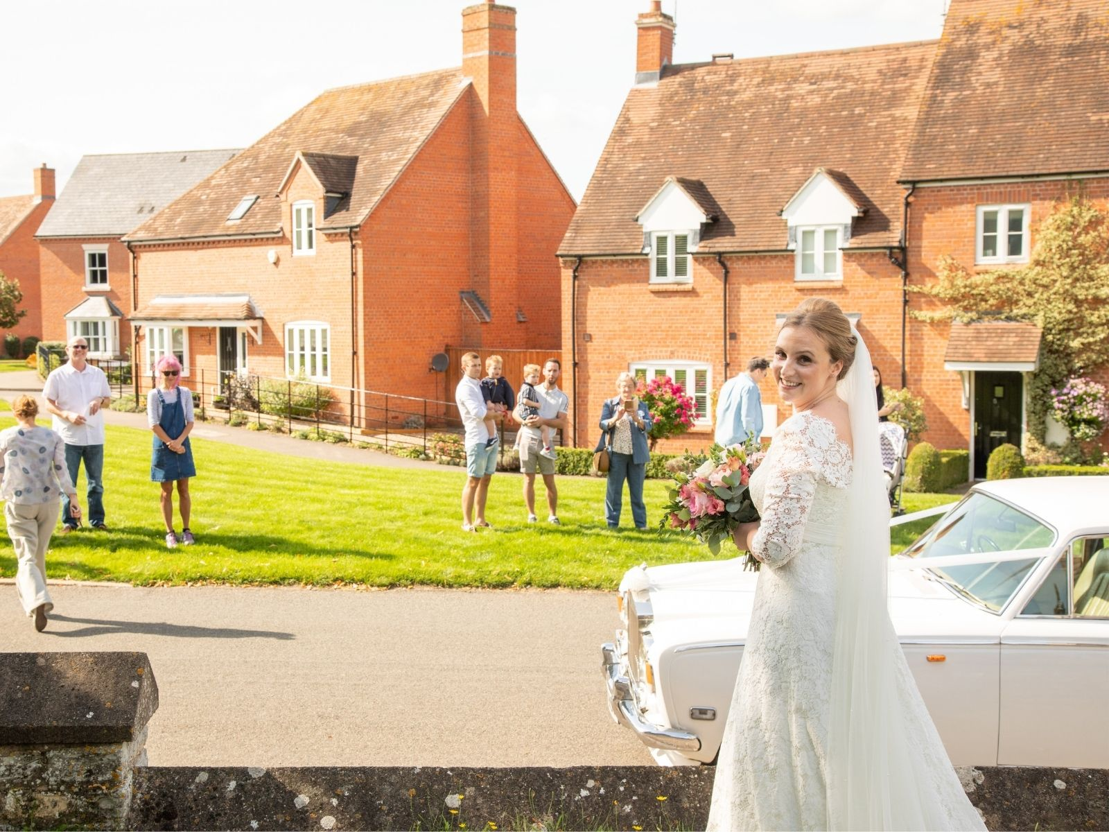 Boho Bride Rachel outside her church, socially distancing from guests on the green opposite